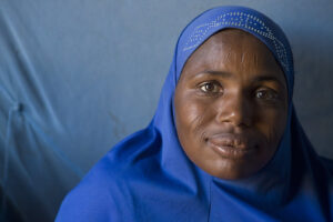 Photo of a Nigerian refugee woman wearing a royal blue headscarf